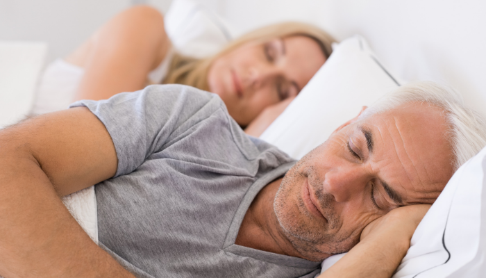 middle aged couple sleeping on side in bed