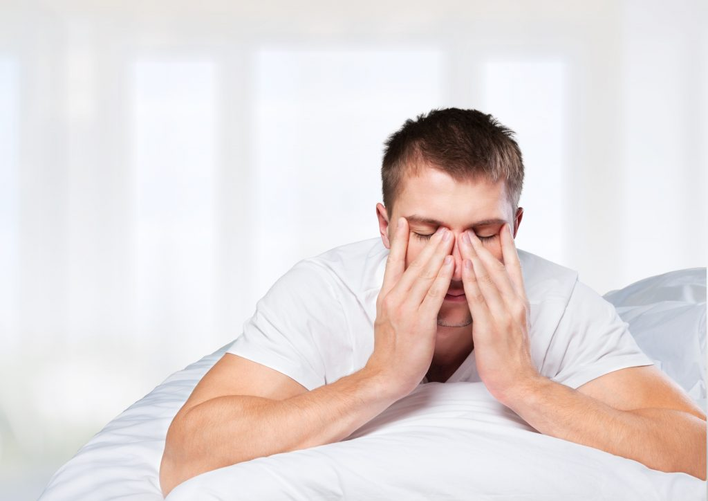 tired man in bed rubbing his eyes