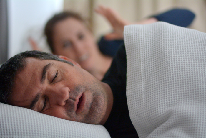 man snoring in bed, wife angry in background