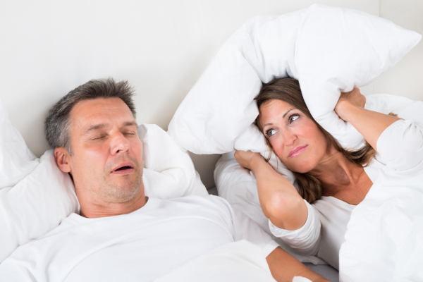 Man Snoring Loudly With Wife Covers Ears With Pillows