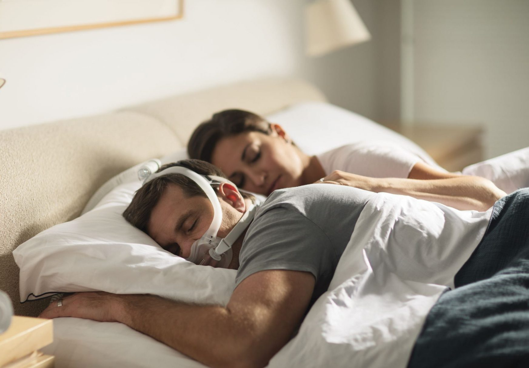 Couple Sleeping Together With CPAP Machine To Assist With Sleeping