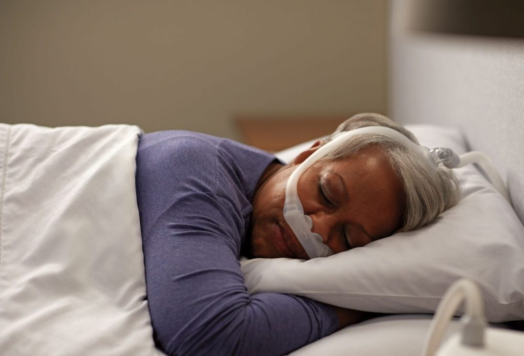 elderly lady sleeping on her side with cpap mask on