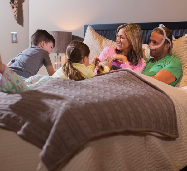 man with cpap mask in bed with wife and daughter playing