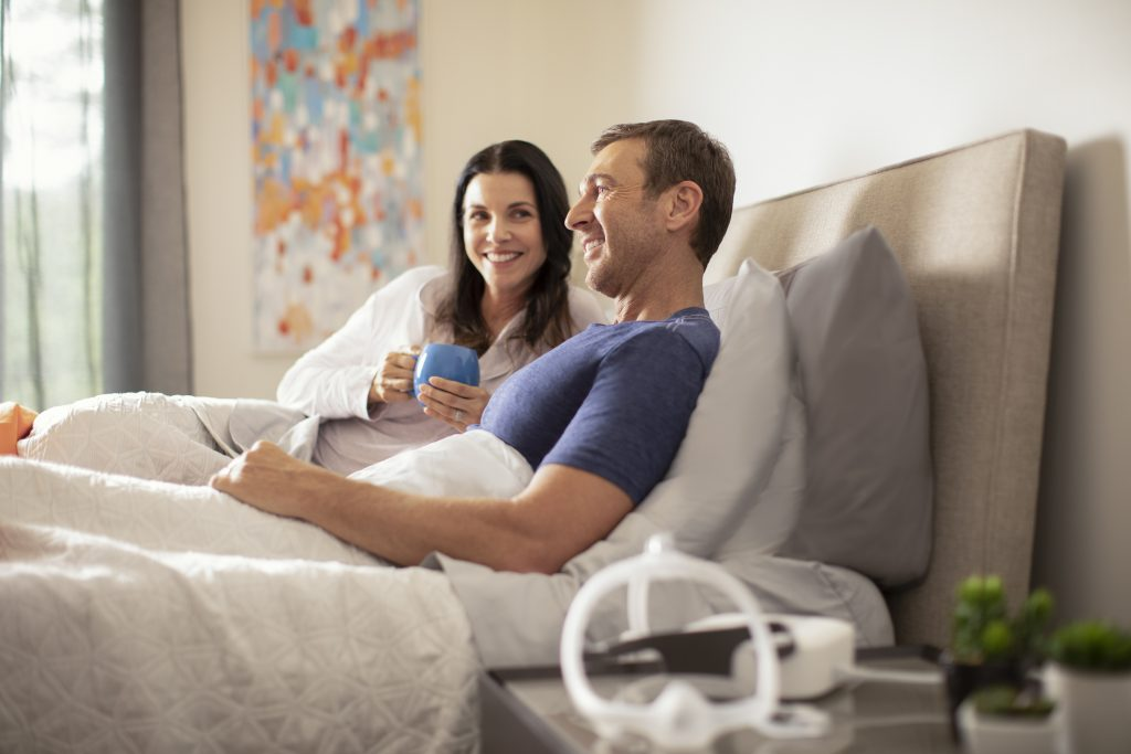 couple in bed with cpap machine on table