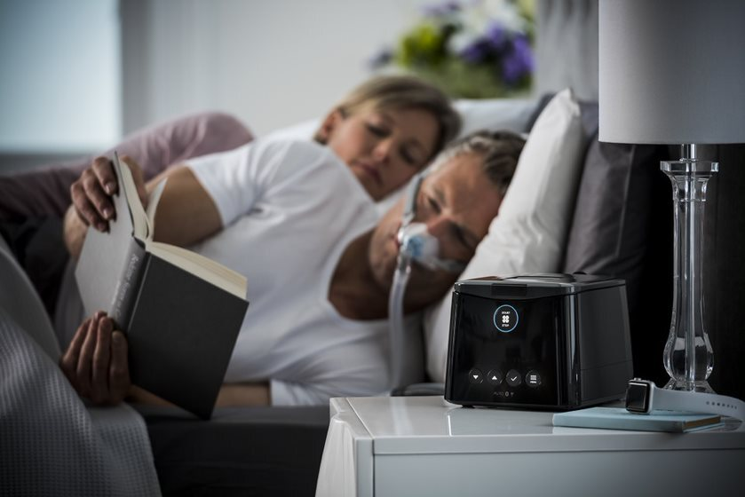 man with his wife with cpap mask on while reading a book